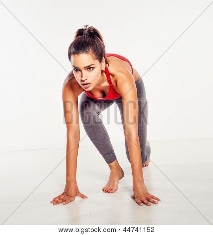 Beautiful athletic woman crouched down in the starter position as though ready to begin a race