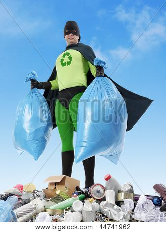 Eco superhero holding two plastic bags full of domestic trash standing on garbage heap - waste segregation concept