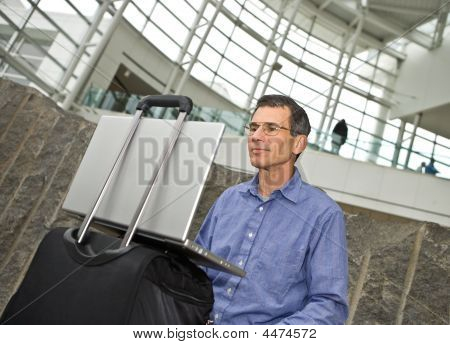 Working On Laptop In Airport Terminal
