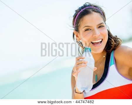 Sports woman drinking water after her workout