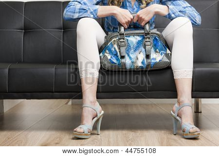 detail of woman wearing summer shoes with a handbag sitting on sofa