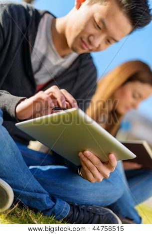 Young Asian Man Holding Digital Tablet; Outdoors