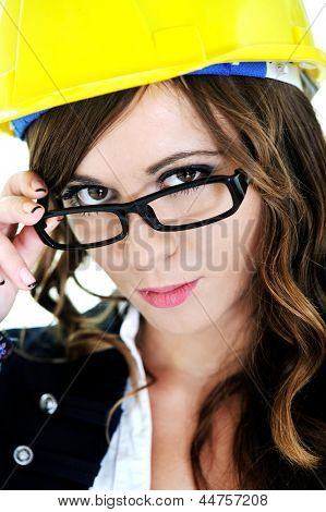Head portrait of young brunette woman with helmet and glasses looking at camera