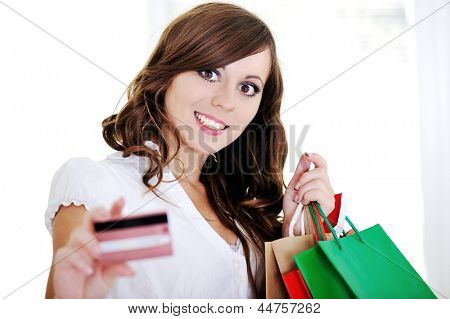 Shopping woman showing business card looking at camera