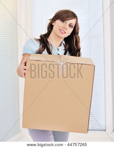 Young woman lifting a heavy cardboard moving box