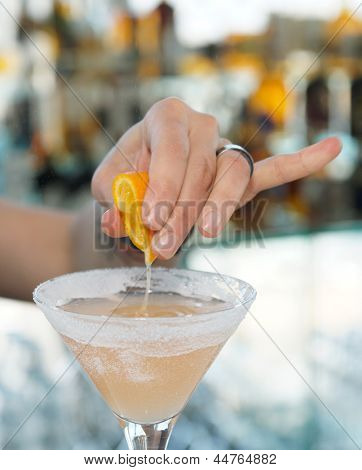 Female bartender is squeezing orange juice into a cocktail glass