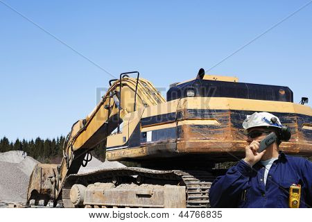 building engineer with giant bulldozer in background