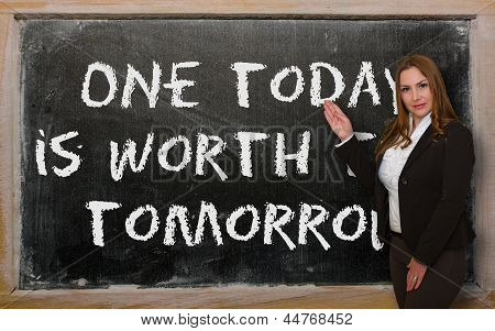 Teacher Showing One Today Is Worth Two Tomorrow On Blackboard