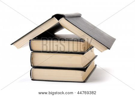 House made with books piled on white background