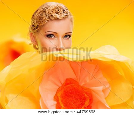 Beautiful young cheerful blond woman among big yellow flowers