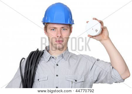 Young electrician holding smoke alarm