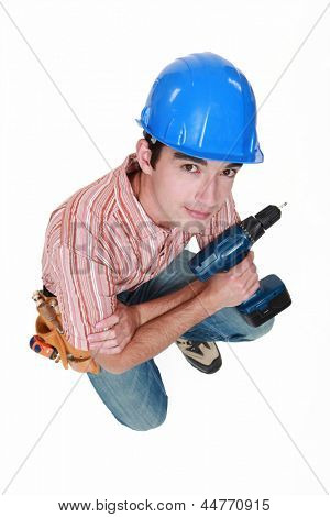 Man with drill kneeling