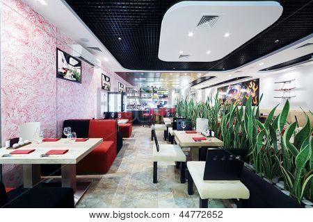 Reihen von Tischen und Stühlen und grüne Blätter in kleinen japanischen Restaurant.