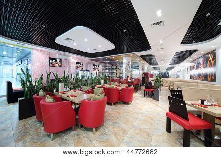 Halle des japanisches Restaurant mit Holztischen, rote Sessel und grünen Blättern.