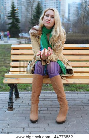 Cute girl with red nails in purple tights sitting on a bench.