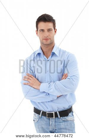 Studio portrait of handsome casual man standing with arms folded, looking at camera, isolated on white.