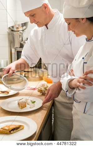 Male baker showing female apprentice serving puff pastry
