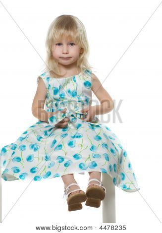Small Blond Girl Sits On White Chair