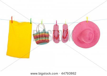 Line with hanging flip flops and pink straw summer hat