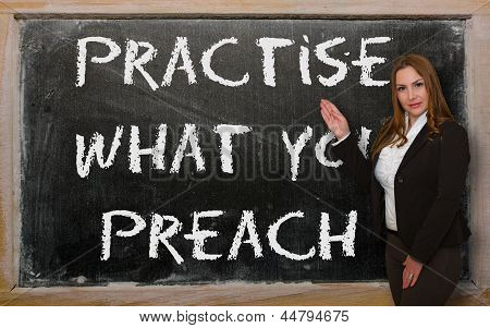 Teacher Showing Practise What You Preach On Blackboard