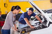 friendly mechanic showing female customer her car problem in garage