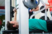 Man with his personal fitness trainer in the gym exercising with dumbbells, he used a barbell on a w