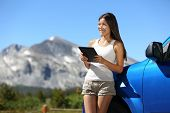 Traveler woman using tablet on Yosemite National Park car road trip vacation travel. Young woman rea