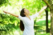 stock photo of greenery  - Young woman meditating with open arms standing in fresh spring greenery with her head raised to the sky and her eyes closed rejoicing in the freshness and new beginnings of spring and nature - JPG