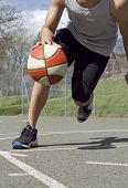 foto of anonymous  - Anonymous basketball player playing basketball on a sunny day