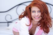 stock photo of harlot  - Seductive redhead girl in bed - JPG