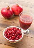 Glass of fresh pomegranate juice and a bowl of seeds