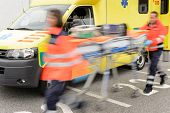 stock photo of ambulance  - Running blurry paramedics team with stretcher and ambulance car - JPG