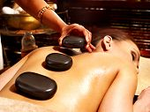 stock photo of hindu  - Young woman having Ayurveda stone massage - JPG