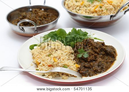 Methi gosht or fenugreek lamb, served with tomato (thakkali) biryani and a leafy salad, with kadasi of the rice and meat behind