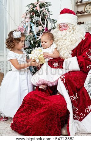 Saint Nicolas gives to small children Christmas gifts