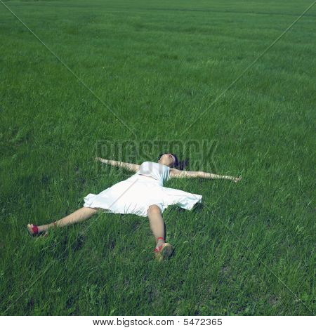 Carefree Young Woman Lays On A Green Grass