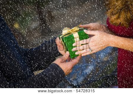 Hands of Man and Woman Exchanging a Wrapped Christmas Gift in the Snow.