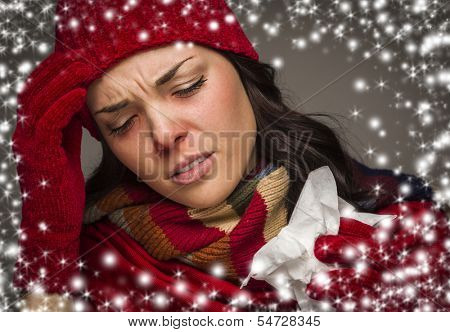 Sick Mixed Race Woman Wearing Winter Hat and Gloves  with a Tissue and Snow Effect Surrounding Her.