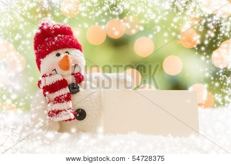 Cute Snowman with Scarf and Hat Next To Blank White Card Over Abstract Snow and Light Background.