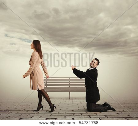 sad man bending the knee before outgoing woman at outdoor