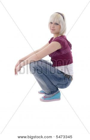 Sitting Jeans Blonde Girl. Side View.