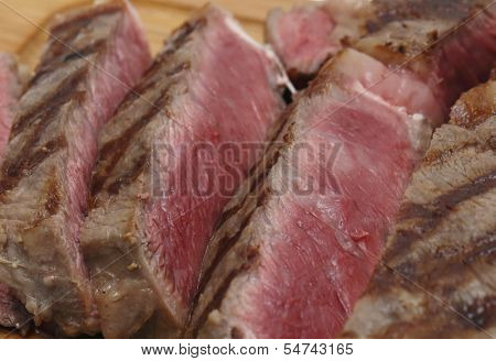 Partly-sliced grilled wagyu beef ribeye steak side view, close-up