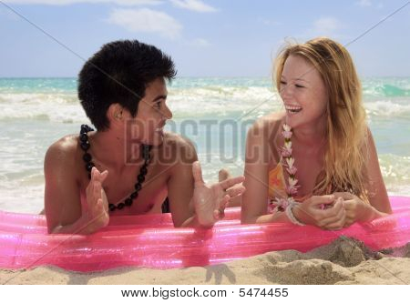 Couple Lying On A Raft At The Beach In Hawaii