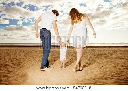 First steps of the kid. Happy family is helping baby takes first steps on the beach