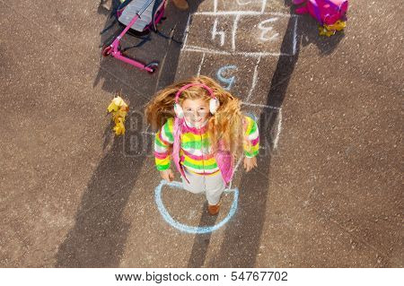 Blond Little Girl Jumps On Hopscotch