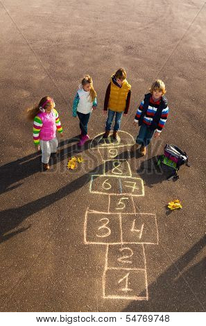 Friends Play Outside On Hopscotch