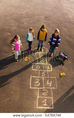 Friends Play Outside On Hopscotch
