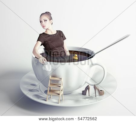 little beautiful woman takes a bath in cup of coffee (creative concept)