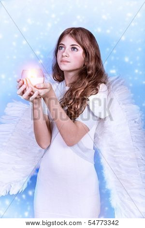 Cute Christmas angel on blue snowy background, adorable girl with candle in hands, religious winter holiday, peace and harmony concept