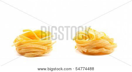 Two fettuccini pasta nests isolated on white.